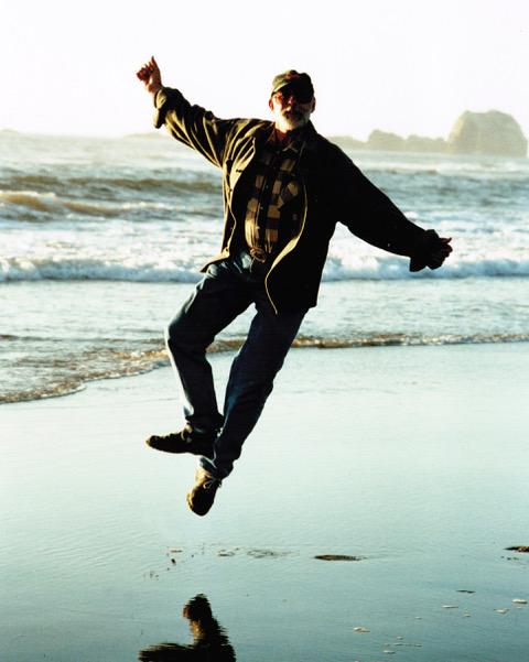 man leaping at ocean's edge